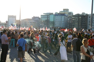 """Demo mit Nelken auf dem Taxim-Platz. Vorne rechts eine """"stillstehende Frau"""""""